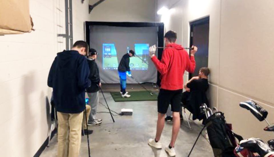 Boys golfers practice shots on the golf simulator