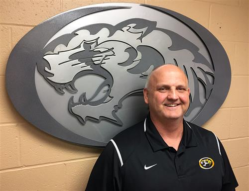 Athletic/Activities Director Rob Davis with tiger logo in background.